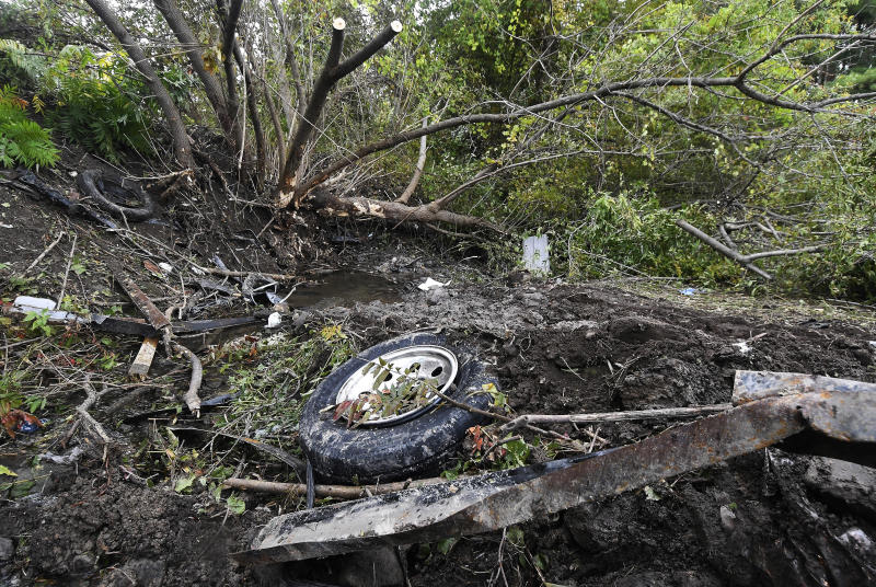 FILE - This Oct. 8, 2018, file photo shows debris scattered in an area at the site of a fatal limousine crash the day before in Schoharie, N.Y. Political leaders in New York have reached an agreement to pass new limousine safety bills inspired by deadly crashes in 2015 and 2018, officials said Tuesday, Jan. 14, 2020. (AP Photo/Hans Pennink, File)