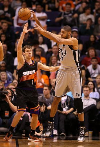 PHOENIX, AZ - FEBRUARY 24: Tim Duncan #21 of the San Antonio Spurs passes the ball around Goran Dragic #1 of the Phoenix Suns during the second half of the NBA game at US Airways Center on February 24, 2013 in Phoenix, Arizona. The Spurs defeated the Suns 97-87. (Photo by Christian Petersen/Getty Images)