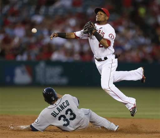 Seattle Mariners' Henry Blanco, left, breaks up a double play after being forced out by Los Angeles Angels shortstop Erick Aybar during the third inning of a baseball game in Anaheim, Calif., Thursday, June 20, 2013. Brendan Ryan was safe at first. (AP Photo/Chris Carlson)