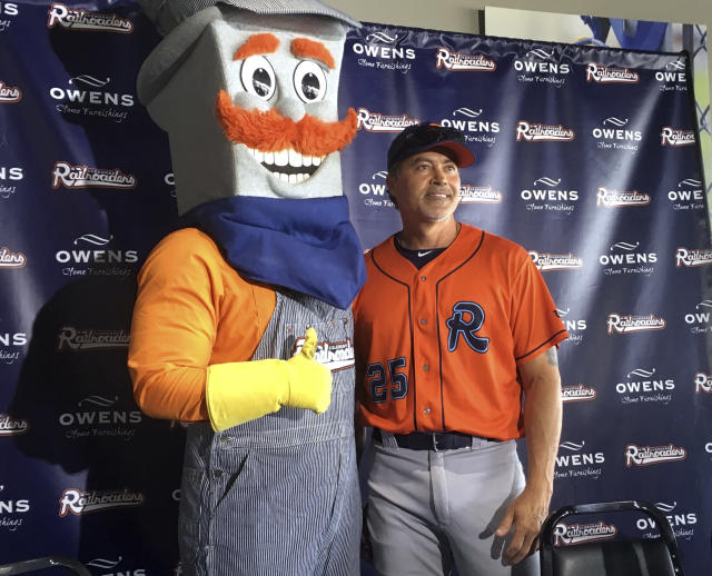 FILE - In this Thursday, May 10, 2018, file photo, the Cleburne Railroaders mascot, Spike, left, poses with former Major League Baseball player and newly-signed player Rafael Palmeiro, right, after a news conference where Palmeiro was introduced in Cleburne, Texas. Palmeiro still has power, even at 53. After hitting more than 500 home runs in the major leagues, Palmeiro homered Monday, May 21, 2018, for the first time in his return to baseball with the independent Cleburne Railroaders. (AP Photo/Stephen Hawkins, File)