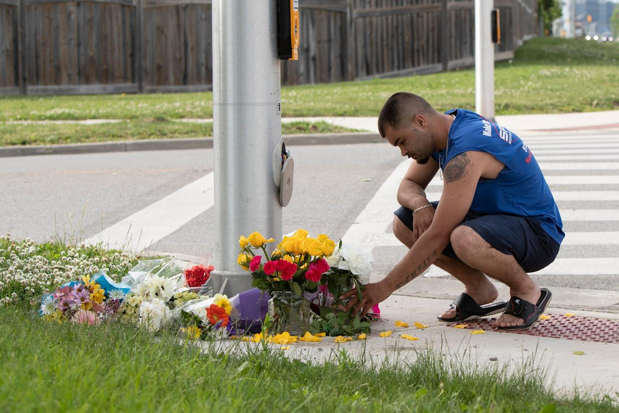 A man brings flowers and pays his respects at the scene where a man driving a pickup truck struck and killed four members of a Muslim family in London, Ontario, Canada on June 7, 2021. - A man driving a pick-up truck slammed into and killed four members of a Muslim family in the south of Canada's Ontario province, in what police said Monday was a