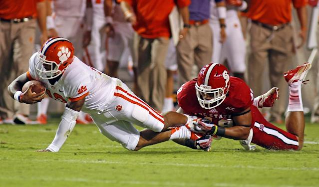 Clemson's Tajh Boyd (10) stretches in the grip of North Carolina States Robert Caldwell (48) during the first half of an NCAA college football game in Raleigh, N.C., Thursday, Sept. 19, 2013. (AP Photo/Karl B DeBlaker)