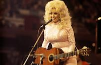 <p>Parton beams in this delightfully bedazzled, all-white outfit while performing at a country music festival in the U.K. </p>