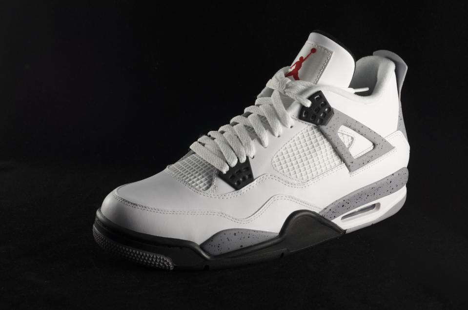 """Bergen County New Jersey, USA- September 8, 2013: A Nike Air Jordan IV shown here in a white and grey colorway. The Nike Air Jordan IV was the first Air Jordan to be released globally. Originally released in 1989, the shoe was re-released in 1999, 2000, 2004, 2006, 2008, 2010, 2011, 2012 and 2013."""