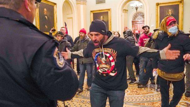 PHOTO: Douglas Jensen from Des Moines, Iowa and other protesters confront U.S. Capitol Police in the hallway outside of the Senate chamber in Washington, Jan. 6, 2021. (Manuel Balce Ceneta/AP)