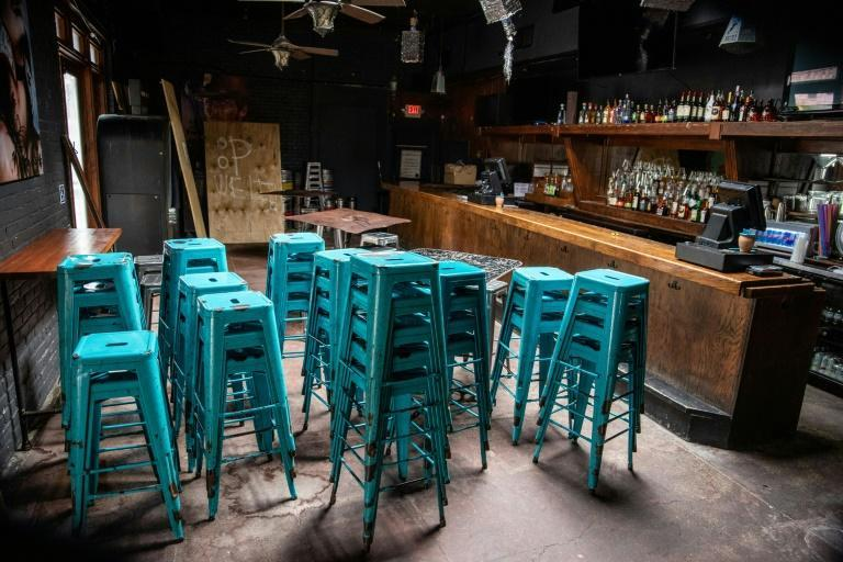 Bar stools piled up in a shuttered bar in Austin Texas in June 2020, during the coronavirus pandemic (AFP Photo/Sergio FLORES)