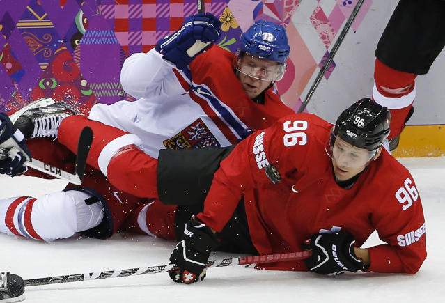 Czech Republic forward Ondrej Palat and Switzerland forward Damien Brunner hit the ice as they battle for the puck in the second period of a men's ice hockey game at the 2014 Winter Olympics, Saturday, Feb. 15, 2014, in Sochi, Russia. (AP Photo/Petr David Josek)