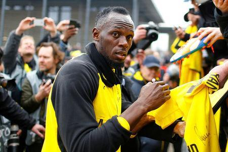 Soccer Football - Usain Bolt participates in a training session with Borussia Dortmund - Strobelallee Training Centre, Dortmund, Germany - March 23, 2018. Usain Bolt signs autographs for fans after Borussia Dortmund training. REUTERS/Thilo Schmuelgen