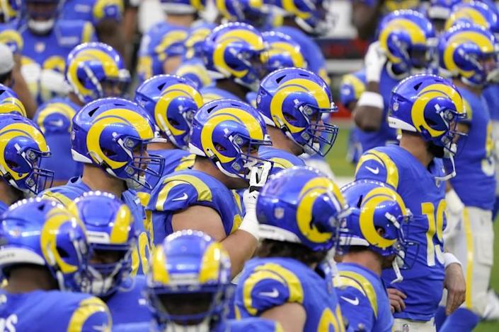 Los Angeles Rams players warm up before an NFL football game against the Arizona Cardinals in Inglewood.