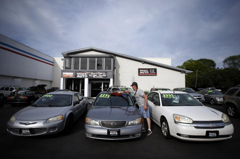 Scott Mimlitsch dusts a used car for sale at Dena's Auto, Tuesday, May 19, 2020 in Runnemede, N.J. New Jersey car and motorcycle dealers along with bike shops shuttered during the COVID-19 pandemic can reopen for in-person sales on Wednesday, Gov. Phil Murphy said Tuesday. (AP Photo/Matt Slocum)