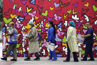 Healthcare workers line up for free personal protective equipment in front of a mural by artist Romero Britto at Jackson Memorial Hospital, Tuesday, Sept. 22, 2020, in Miami. Hundreds of workers lined up for the PPE given out by the New York nonprofit Cut Red Tape 4 Heroes. (AP Photo/Wilfredo Lee)