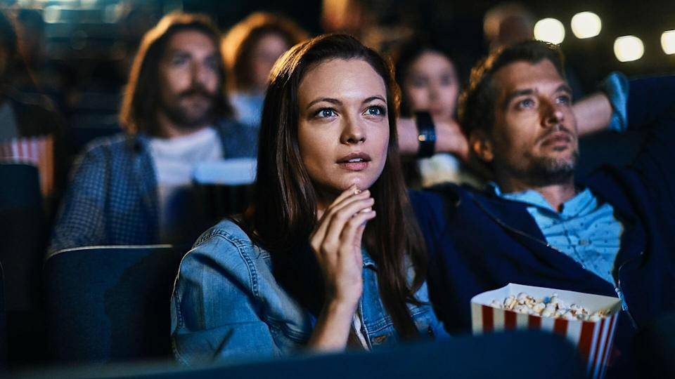 Close up of a couple enjoying a movie in the cinema.
