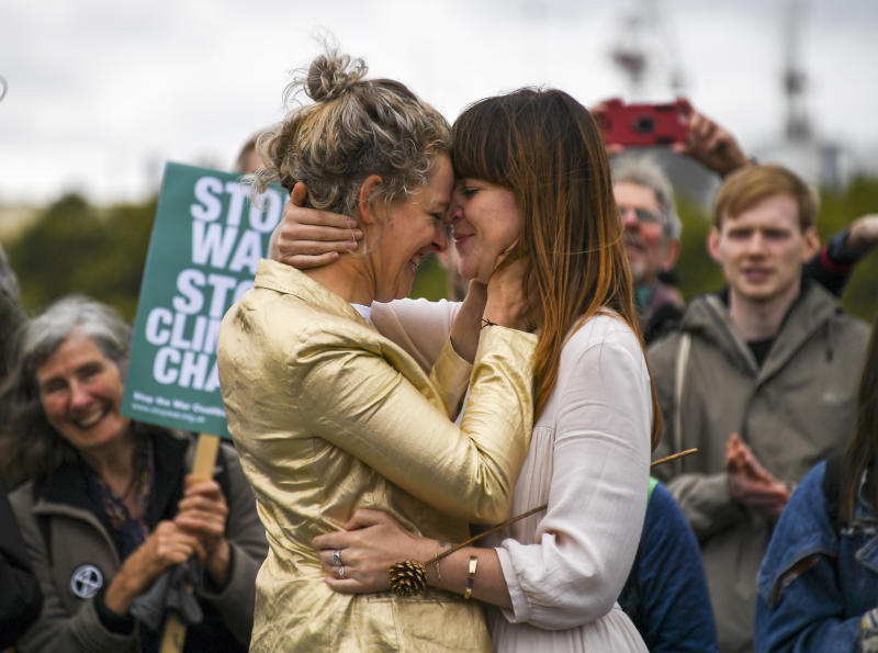 Two women celebrate their marriage on Westminster Bridge, during an Extinction Rebellion protest in London, Monday, Oct. 7, 2019. Demonstrators playing steel drums marched through central London on Monday as they kicked off two weeks of activities designed to disrupt the city. London Police say some 135 climate activists have been arrested as the Extinction Rebellion group attempts to draw attention to global warming. (AP Photo/Alberto Pezzali)