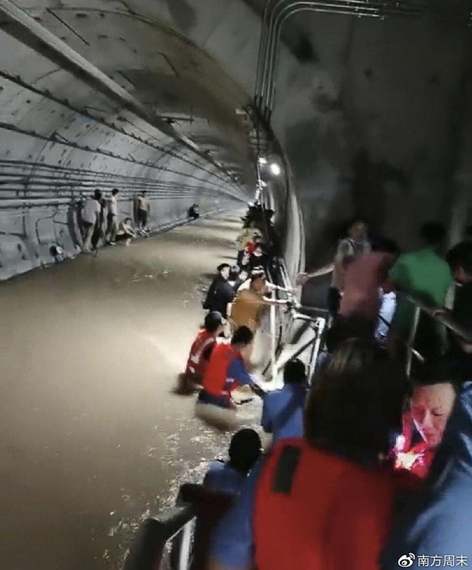 Rescuers help passengers climb to safety as water pours into the subway tunnels in Zhengzhou. Photo: Weibo