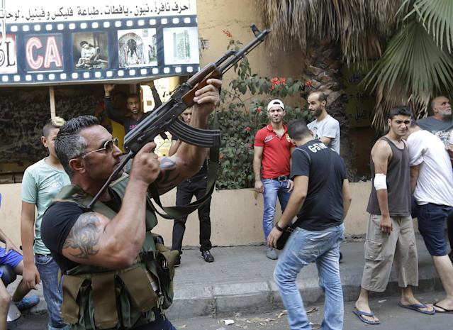 A Lebanese Shiite gunman fires his AK-47 during the funeral procession of Hamad al-Mekdad, 42, who was killed on Thursday by a car bomb explosion at an predominantly Shiite area and stronghold of the Lebanese militant group Hezbollah, in the southern suburb of Beirut, Lebanon, Friday, Aug. 16, 2013. Lebanese forensic experts collected evidence Friday at the scene of a massive explosion in a southern suburb of Beirut that killed dozens of people and wounded hundreds, the deadliest blast in the area in nearly three decades. (AP Photo/Hussein Malla)