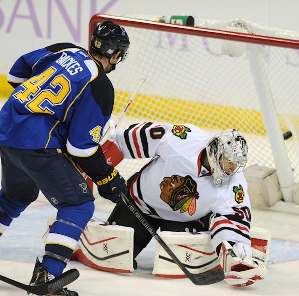 Chicago Blackhawks' goalie Corey Crawford, right, is scored on by St. Louis Blues' David Backes (42) during the second period of an NHL hockey game Wednesday, Oct. 9, 2013, in St. Louis. (AP Photo/Bill Boyce)