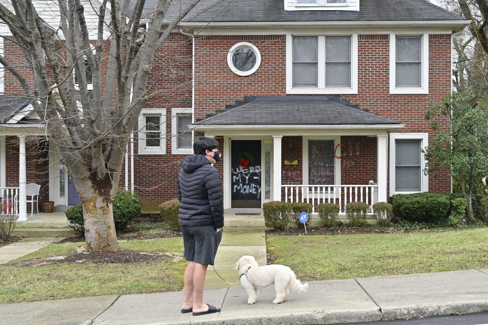 A neighbor looks at the spray paint on the front of the home of Senate Majority Leader Mitch McConnell, r, Ky., which was vandalized overnight in Louisville, Ky., Saturday, Jan. 2, 2021. (AP Photo/Timothy D. Easley)