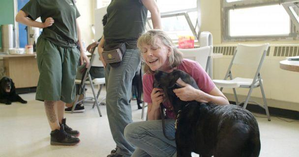 PHOTO: Jeanne Meyer greets her new dog Angel, who she received from the program Puppies Behind Bars. (Laurie White/Puppies Behind Bars)
