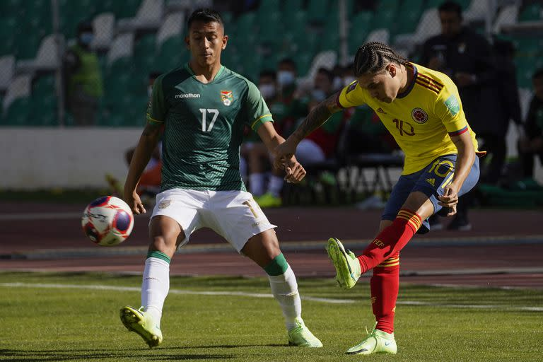 Colombia's Juan Quintero (R) strikes the ball as Bolivia's Roberto Carlos Fernandez looks on during their South American qualification football match for the FIFA World Cup Qatar 2022 at the Hernando Siles Olympic Stadium in La Paz on September 2, 2021. (Photo by Javier MAMANI / POOL / AFP)