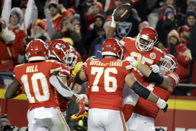 Kansas City Chiefs offensive guard Andrew Wylie (77) picks up celebrating running back LeSean McCoy (25) after McCoy scored a touchdown during the second half of an NFL football game against the Oakland Raiders in Kansas City, Mo., Sunday, Dec. 1, 2019. (AP Photo/Charlie Riedel)