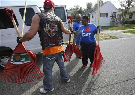 Mayor Karen Freeman-Wilson (R) receives assistance from a volunteer in a neighborhood clean-up project in Gary, Indiana, September 28, 2013. REUTERS/Jim Young