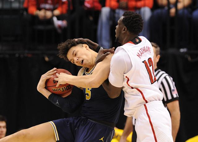 <p>Michigan Wolverines forward D.J. Wilson (5) battles for the ball with Louisville Cardinals forward Mangok Mathiang (12) during the first half in the second round of the 2017 NCAA Tournament at Bankers Life Fieldhouse. Mandatory Credit: Thomas Joseph-USA TODAY Sports </p>