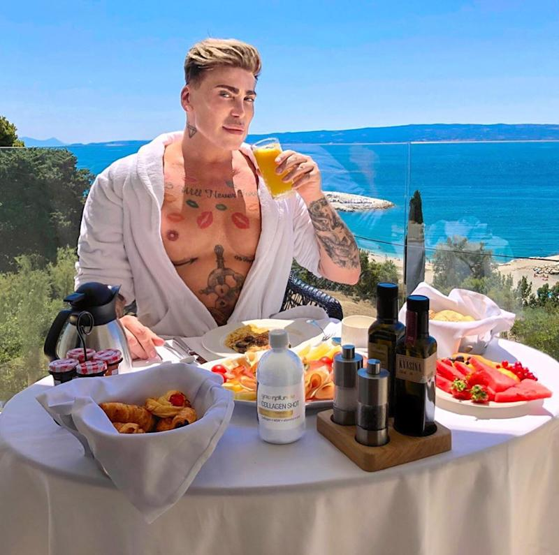 A photo of Neven Ciganovic from Zagreb, Croatia, wearing a white robe while sitting on a balcony eating breakfast
