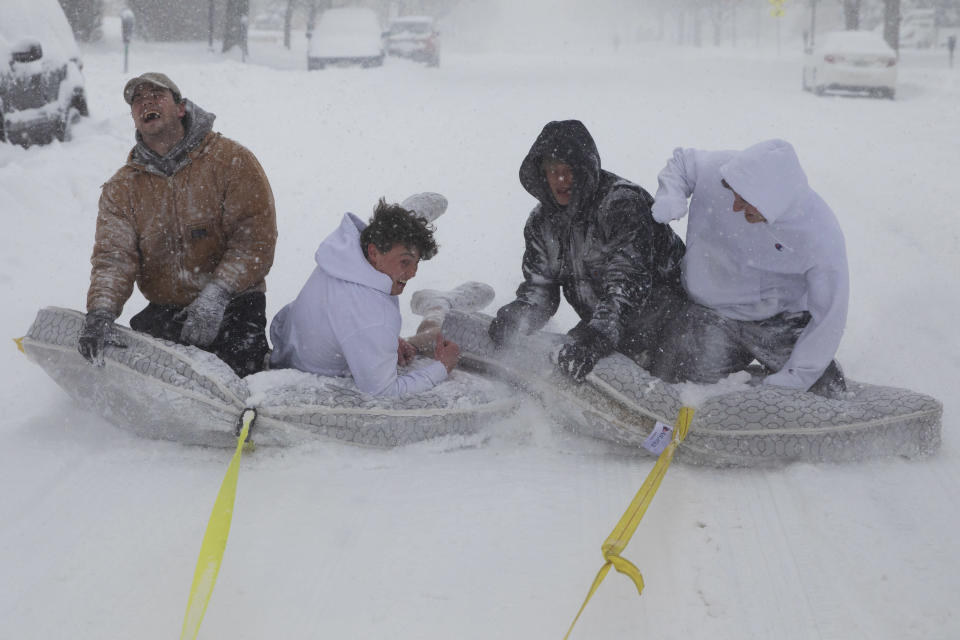 Brothers of the Phi Gamma Delta Fraternity pull their friends on mattresses along the street in front of the UNL Union during a winter storm in downtown Lincoln, Neb. on Monday, Jan. 25, 2021. (Kenneth Ferriera/Lincoln Journal Star via AP)