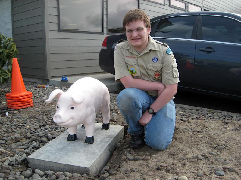 """This undated photo supplied by the Astoria Police Department shows Michael Peden, 16, an Eagle Scout candidate, with a concrete pig he helped restore for the police department in Astoria, Ore. The pig was dropped off in 1993 by someone whose motive wasn't clear and two decades have taken their toll, washing off the pink paint, pitting the surface and loosening the ears.  Now, the department has stationed the restored pig in a more prominent location, as it said in a press release, """"at the entrance to the Police Department parking area, watching the comings and goings of police officers."""" (AP Photo/Astoria Police Department)"""