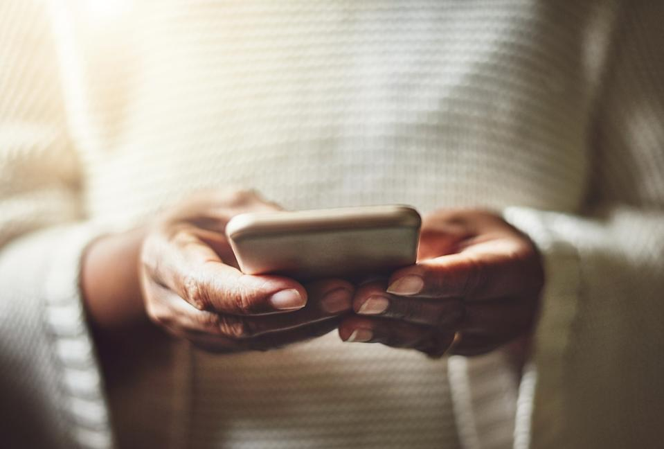 Closeup shot of an unrecognizable woman using a cellphone at home