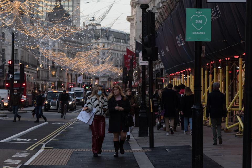 Shoppers and commuters walk along Oxford Street ahead of introduction of tougher coronavirus restrictions in the run up to Christmas, on 15 December, 2020 in London, England. From tomorrow, Greater London, as well as parts of Essex and Hertfordshire, will move into Tier 3 coronavirus restrictions resulting in closing of pubs, bars, restaurants, hotels and indoor entertainment venues such as theatres and cinemas, as the infection rates are well above the national average and continue to rise. (Photo by WIktor Szymanowicz/NurPhoto via Getty Images)