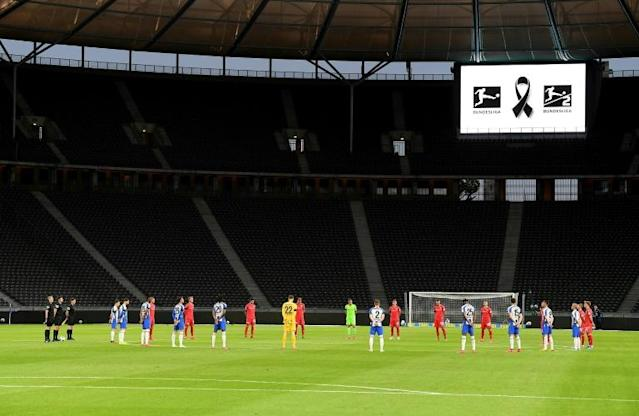 Empty feeling: Players hold a minute's silence ahead of the game at the Olympic Stadium (AFP Photo/Stuart Franklin)