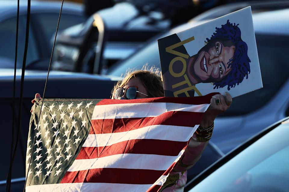 SAVANNAH, GEORGIA - JANUARY 03: A woman waves an American flag as she holds a painting of Stacey Abrams as she listens to Democratic Senate candidate Rev. Raphael Warnock speak during a drive-in rally at Garden City Stadium on January 03, 2021 in Savannah, Georgia. Vice President-elect Kamala Harris joined Warnock and fellow Democratic Senate candidate Jon Ossoff for a campaign event two days before the January 5th runoff election that has implications into which party controls the U.S. Senate. According to AJC, 3 million people have already casted their votes ahead of Tuesday's election.  (Photo by Michael M. Santiago/Getty Images)