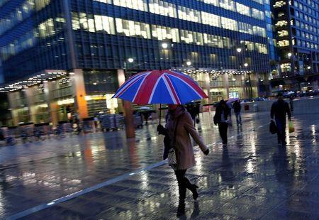 FILE PHOTO - Workers walk in the rain at the Canary Wharf business district in London