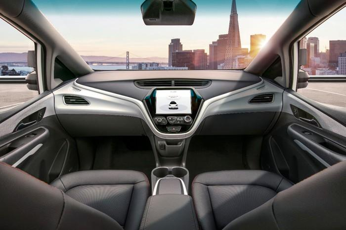 The front seats and dashboard of a Cruise AV, showing that the vehicle has no steering wheel.