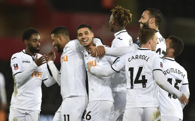 Swansea City's Kyle Naughton (centre) celebrates with his team-mates after scoring his side's fifth goal against Notts County during the Emirates FA Cup, fourth round replay match at the Liberty Stadium in Swansea, England, Tuesday Feb. 6, 2018. (Simon Galloway/PA via AP)