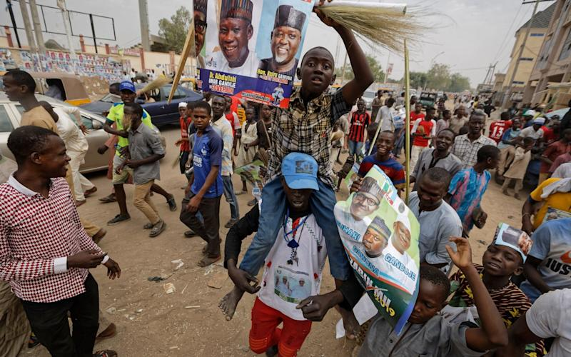 Supporters of Nigeria's President Muhammadu Buhari march to celebrate his electoral win - AP
