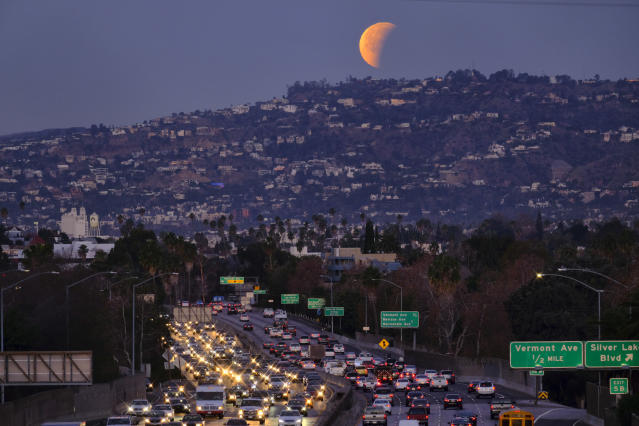 <p>A super blue blood moon is seen setting behind the Hollywood hills in Los Angeles on Wednesday Jan. 31, 2018. (Photo: Richard Vogel/AP) </p>