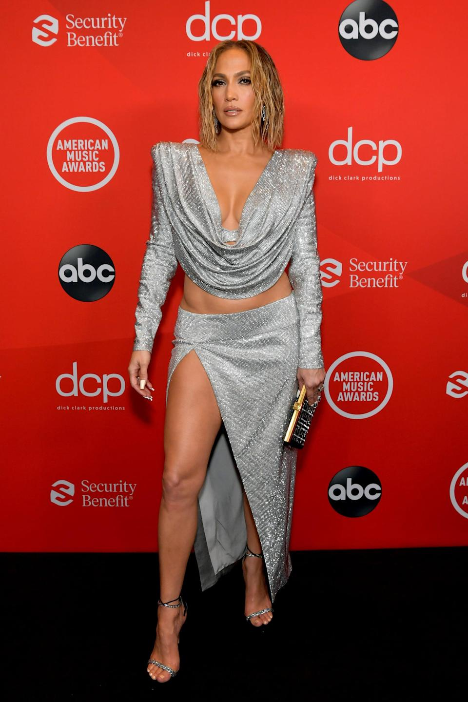 "<p><a href=""https://www.popsugar.com/fashion/jennifer-lopez-american-music-awards-2020-outfit-47994496"" class=""link rapid-noclick-resp"" rel=""nofollow noopener"" target=""_blank"" data-ylk=""slk:Wearing a Balmain look"">Wearing a Balmain look</a> with jewels by Luminous Diamonds. See <a href=""https://www.popsugar.com/fashion/jennifer-lopez-american-music-awards-bodysuit-2020-47995095"" class=""link rapid-noclick-resp"" rel=""nofollow noopener"" target=""_blank"" data-ylk=""slk:her LaQuan Smith performance look here"">her LaQuan Smith performance look here</a>.</p>"