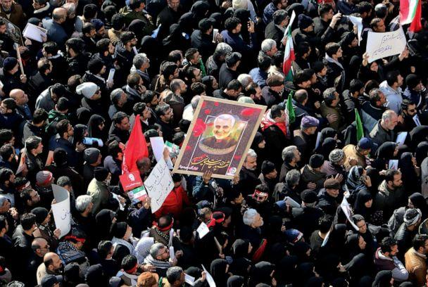 PHOTO: Iranian mourners lift a picture of slain military commander Qassem Soleimani during a funeral procession in Tehran, Jan. 6, 2020, for him as well as Iraqi paramilitary chief Abu Mahdi al-Muhandis and other victims of a U.S. drone strike. (Atta Kenare/AFP via Getty Images)