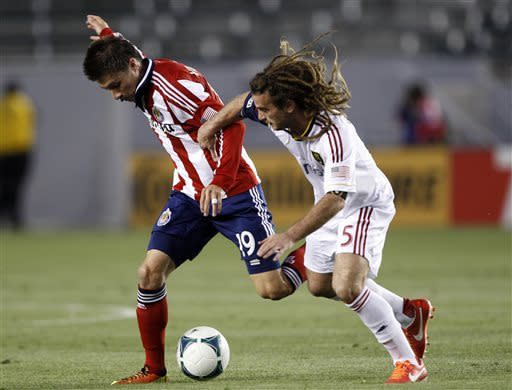 Chivas USA defender Jorge Villafana, left, tangles with Real Salt Lake midfielder Kyle Beckerman (5) for the ball during the first half of an MLS soccer game in Carson, Calif., Sunday, May 19, 2013. (AP Photo/Alex Gallardo)