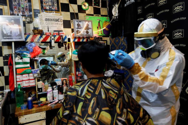 Herman Maulanasyah, a 40-year-old hair stylist, gives a haircut to a customer at his barbershop, while wearing a handmade protective suit in a tribute to the country's medical workers tackling the coronavirus disease (COVID-19) in Bogor