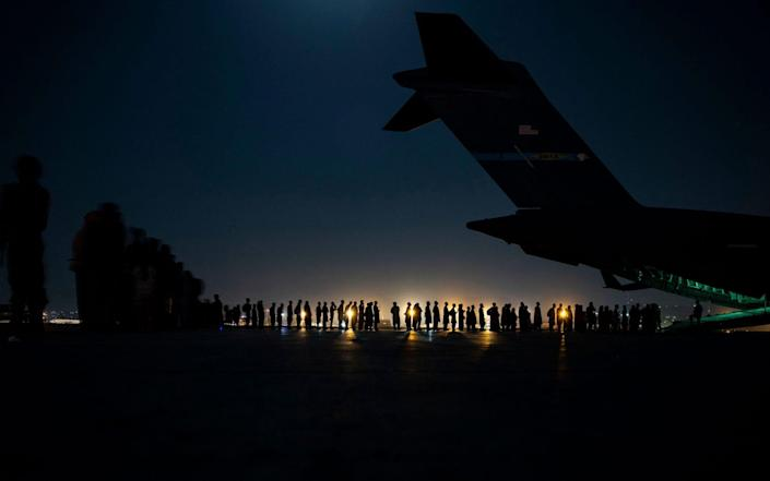 a US Air Force aircrew, assigned to the 816th Expeditionary Airlift Squadron, prepare to load qualified evacuees aboard a US Air Force C-17 Globemaster III aircraft in support of Afghanistan evacuation at Hamid Karzai International Airport - TAYLOR CRUL