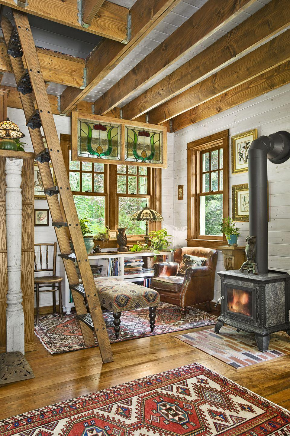 """<p>When square footage is tight, it helps if statement pieces are both charming and useful. An old wood-burning stove brings a vintage vibe to new construction and also heats the entire place.</p><p><a class=""""link rapid-noclick-resp"""" href=""""https://www.amazon.com/Tiny-House-Living-Building-Square/dp/1440333165/?tag=syn-yahoo-20&ascsubtag=%5Bartid%7C10050.g.1887%5Bsrc%7Cyahoo-us"""" rel=""""nofollow noopener"""" target=""""_blank"""" data-ylk=""""slk:SHOP TINY HOUSE BOOKS"""">SHOP TINY HOUSE BOOKS</a></p>"""