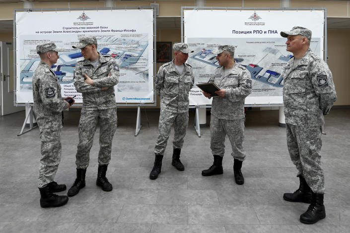 """Russian officers talk to each other at a central atrium called the """"Arctic Trefoil"""" on the Alexandra Land island near Nagurskoye, Russia, Monday, May 17, 2021. Once a desolate home mostly to polar bears, Russia's northernmost military outpost is bristling with missiles and radar and its extended runway can handle all types of aircraft, including nuclear-capable strategic bombers, projecting Moscow's power and influence across the Arctic amid intensifying international competition for the region's vast resources. (AP Photo/Alexander Zemlianichenko)"""