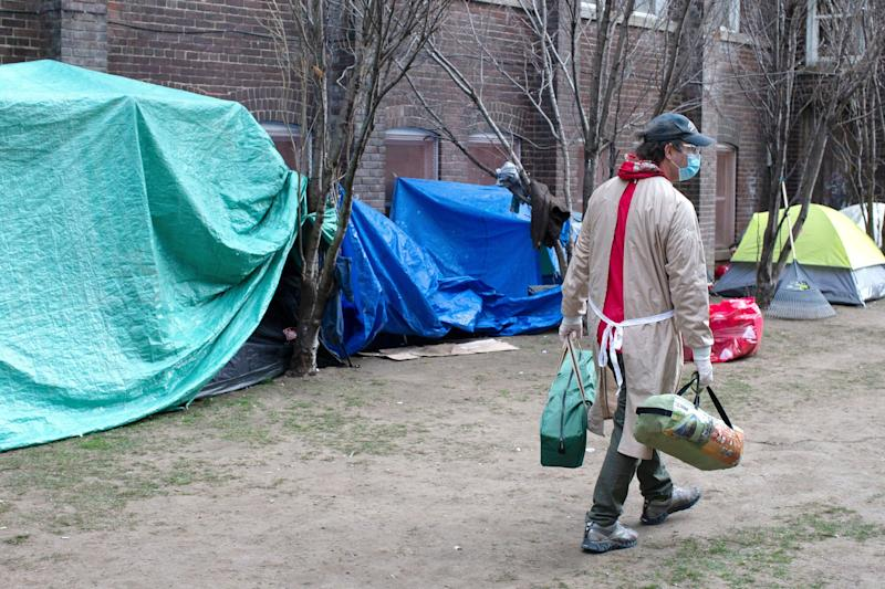 Doug Johnson Hatlem, a worker at The Sanctuary, a respite centre in Toronto, carries tents to be distributed to members of the homeless community on April 19 2020. (Photo: Chris Young/THE CANADIAN PRESS)