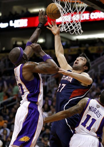Atlanta Hawks' Zaza Pachulia (27), of Georgia, shoots over Phoenix Suns' Jermaine O'Neal, left, during the first half of an NBA basketball game, Friday, March 1, 2013, in Phoenix. (AP Photo/Matt York)