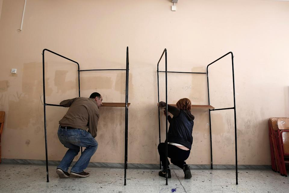 Municipal workers assemble voting booths at a voting center in Athens, Friday, Jan. 23, 2015. (AP Photo/Petros Giannakouris)
