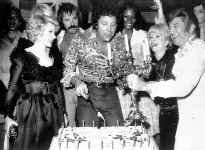 Tom Jones, center, blows out candles at a surprise birthday party at Caesars Palace, Las Vegas, June 6, 1974. Guests include, from left to right, Joan Rivers, Sonny Bono, Jones, Debbie Reynolds, and Liberace. (AP Photo)