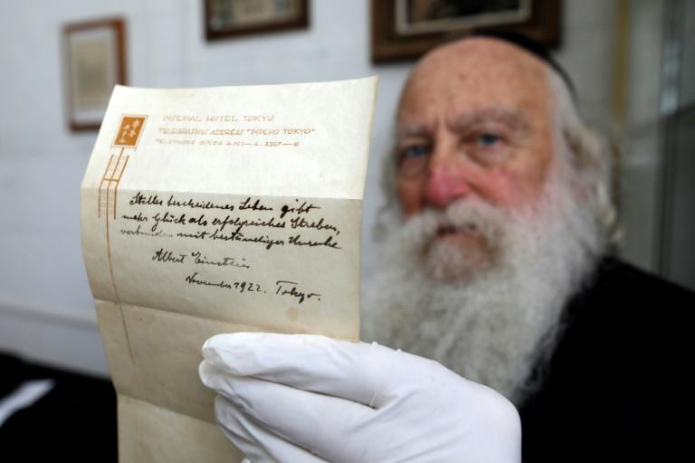 An Ultra-Orthodox Jewish man displays a note written by Albert Einstein in 1922 on hotel stationary from the Imperial Hotel in Tokyo, Japan, at the Winner's auction house in Jerusalem on October 19, 2017